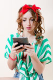 读&拿着有红色嘴唇的片剂个人计算机计算机美丽的白肤金发的少妇画报女孩&丝带在她的在轻的背景的头 免版税库存照片