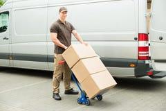 拿着有纸板箱的送货人台车 免版税图库摄影