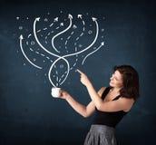 拿着有线和箭头的女实业家一个白色杯子 库存照片
