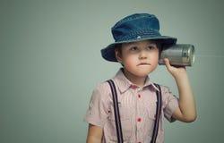 拿着有绳子的小男孩一个罐头 图库摄影