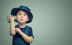 拿着有绳子的小男孩一个罐头 库存图片
