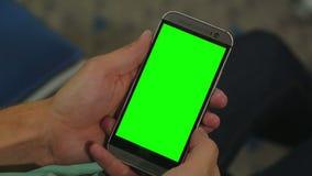 拿着有绿色屏幕的男性手特写镜头巧妙的电话为作用prekeyed 股票录像