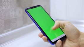 拿着有绿色屏幕的男性手特写镜头智能手机前锁上为作用 移动和键入在屏幕上 股票视频