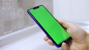 拿着有绿色屏幕的男性手特写镜头智能手机前锁上为作用 股票录像