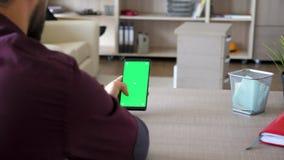 拿着有绿色屏幕色度嘲笑的人一个智能手机在手上 影视素材