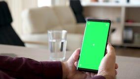 拿着有绿色屏幕色度嘲笑的男性手显露的射击一个智能手机 影视素材