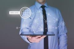 拿着有联机服务文本的商人一台片剂个人计算机在虚屏上 背景蓝色颜色概念互联网 免版税图库摄影