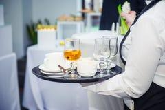 拿着有肮脏的盘的侍者盘子在事件的客人以后 承办酒席服务在业务会议,党,婚礼上 食物C 免版税库存图片