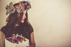 拿着有花和蛋白杏仁饼干曲奇饼的妇女一个箱子 免版税库存图片