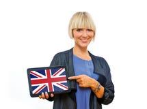 拿着有英国旗子的可爱的白肤金发的妇女片剂 免版税图库摄影