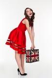 拿着有英国旗子的快乐的可爱的卷曲妇女葡萄酒手提箱 库存照片