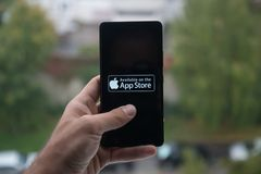 拿着有苹果计算机app商店商标的人智能手机与在屏幕上的手指 库存照片