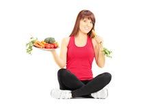 拿着有菜和红萝卜的年轻美丽的妇女板材 图库摄影