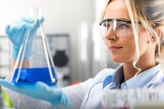 拿着有蓝色liqu的年轻可爱的女性科学家一个烧瓶 免版税库存照片