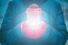 拿着有蜡烛关闭的人一个红色蜡烛灯笼 免版税库存图片