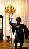 拿着有蜡烛的卫兵雕象金黄枝形吊灯 免版税库存照片