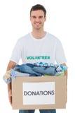 拿着有衣裳的可爱的人捐赠箱子 免版税库存照片