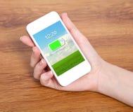 拿着有被充电的电池的妇女手一个接触白色电话在a 库存照片