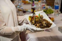 拿着有被浇灌的棕色沙司肉饮食的白色手套的一位女服务员一块板材  免版税库存图片