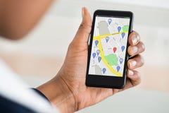 拿着有装配标记的妇女的手手机在地图 免版税库存图片