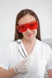 拿着有角度的镜子和卡佛的牙齿护士 库存图片