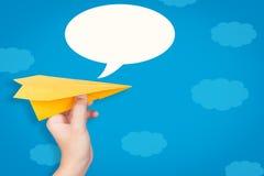 拿着有讲话泡影的手纸飞机 免版税库存照片