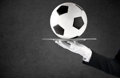 拿着有足球的一个盘子的侍者 头等服务的概念在足球的 免版税库存照片