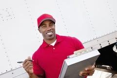 拿着有送货卡车的一个愉快的非裔美国人的人的画象剪贴板在背景中 免版税库存图片
