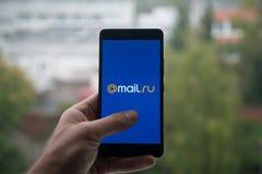 拿着有邮件的人智能手机 与手指的ru商标在屏幕上 免版税图库摄影