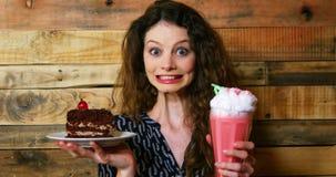 拿着有酥皮点心和冰淇凌浮游物的女性顾客画象板材 影视素材