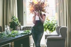 拿着有野花夏天花束的俏丽的妇女花瓶在她的手上在有桌和耳朵扶手椅子的客厅在窗口 库存照片