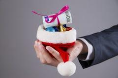 拿着有金钱的商人圣诞老人帽子 库存图片