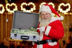 拿着有金钱的圣诞老人手提箱 免版税库存图片