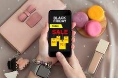 拿着有销售黑色星期五屏幕的女性手手表电话 免版税库存图片