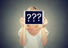 拿着有问号的妇女片剂个人计算机掩藏她的面孔 免版税库存图片