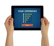 拿着有顾客回顾概念的手片剂在屏幕上 免版税图库摄影
