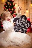 拿着有题字圣诞快乐的孩子委员会 库存图片
