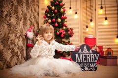 拿着有题字圣诞快乐的孩子委员会 库存照片