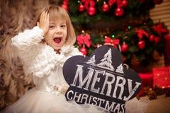拿着有题字圣诞快乐的孩子委员会 免版税库存图片