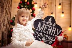 拿着有题字圣诞快乐的孩子委员会 免版税图库摄影