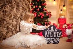 拿着有题字圣诞快乐的孩子委员会 免版税库存照片