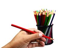 拿着有颜色的手一支红颜色铅笔在黑加州书写 库存图片