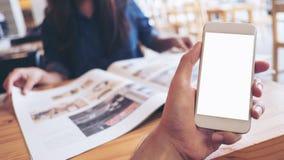 拿着有黑屏的人` s手的大模型图象白色手机在现代咖啡馆和迷离妇女读书报纸 库存图片
