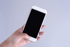 拿着有黑屏幕的手白色智能手机 免版税图库摄影