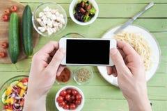 拿着有黑屏的智能手机和拍摄意粉和新鲜蔬菜在木桌上的人 免版税库存图片