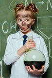 拿着有黑板的白色外套烧瓶后边在科学实验室 库存图片