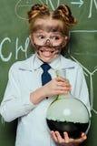 拿着有黑板的白色外套的女孩烧瓶后边在科学实验室 图库摄影