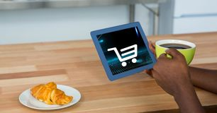 拿着有购物车象的人的播种的图象数字式片剂在屏幕上,当食用咖啡时 图库摄影