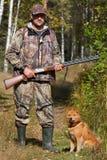 拿着有他的狗的猎人一杆枪 免版税库存照片