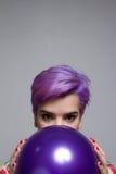 拿着有他的紫罗兰色短发妇女的特写镜头一个气球 免版税库存照片